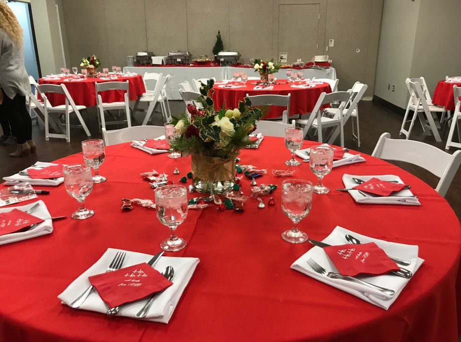 Table decorated with red and white flower centerpieces