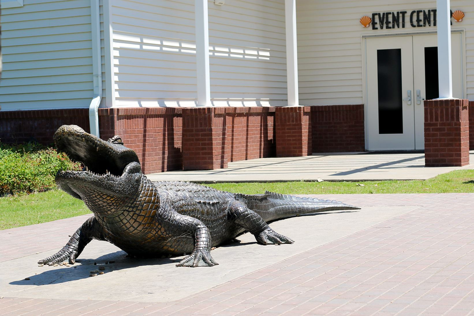 A bronze statue of an alligator in front of a white building.